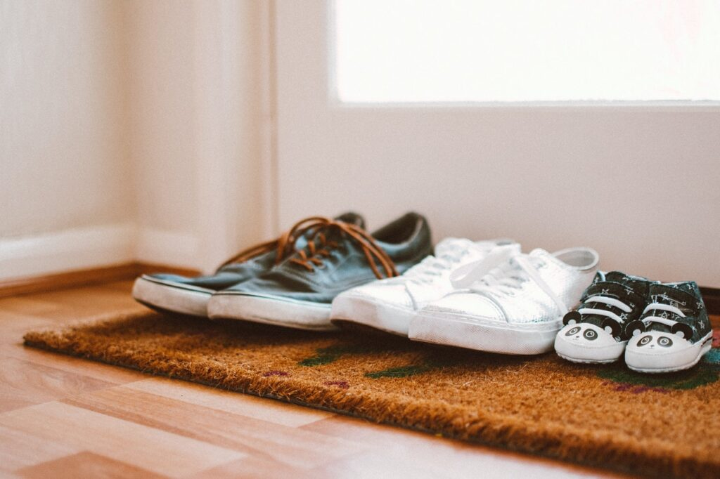 family shoes on a rug in front of a door