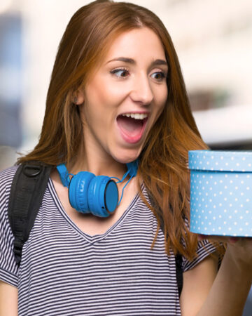 Redhead student woman holding gift box in hands in the city