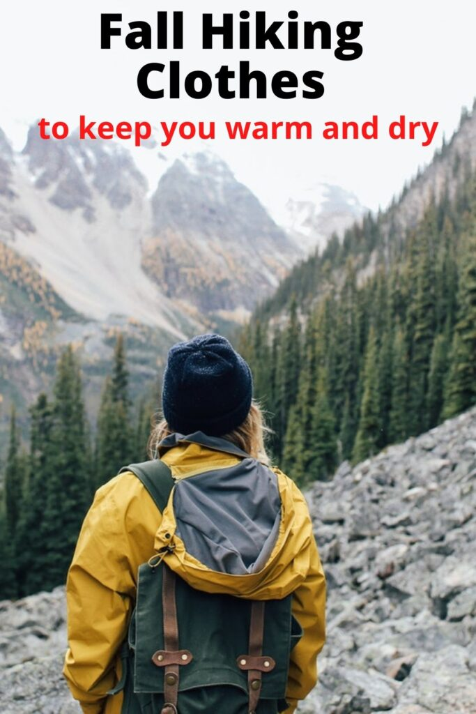 woman hiking on mountain in fall wearing hat and rain jacket with text overlay Fall Hiking Clothes that keep you warm and dry