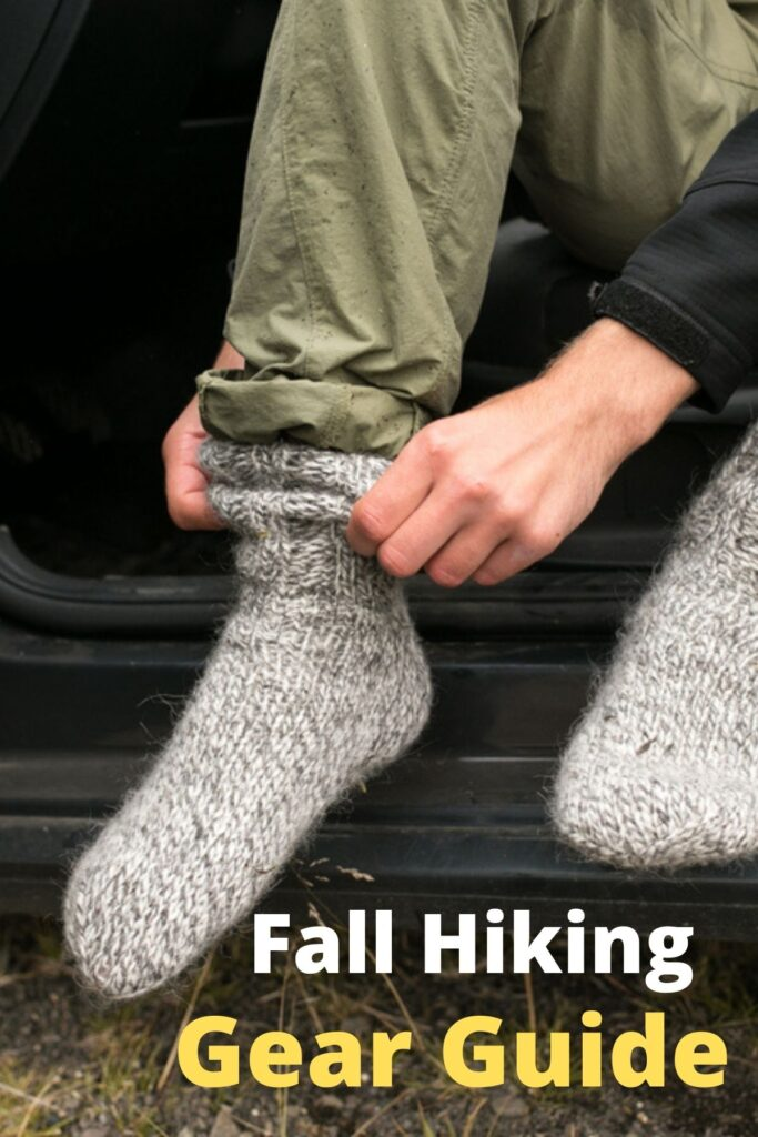 person putting on warm wool socks with text overlay 'Fall Hiking Gear Guide'