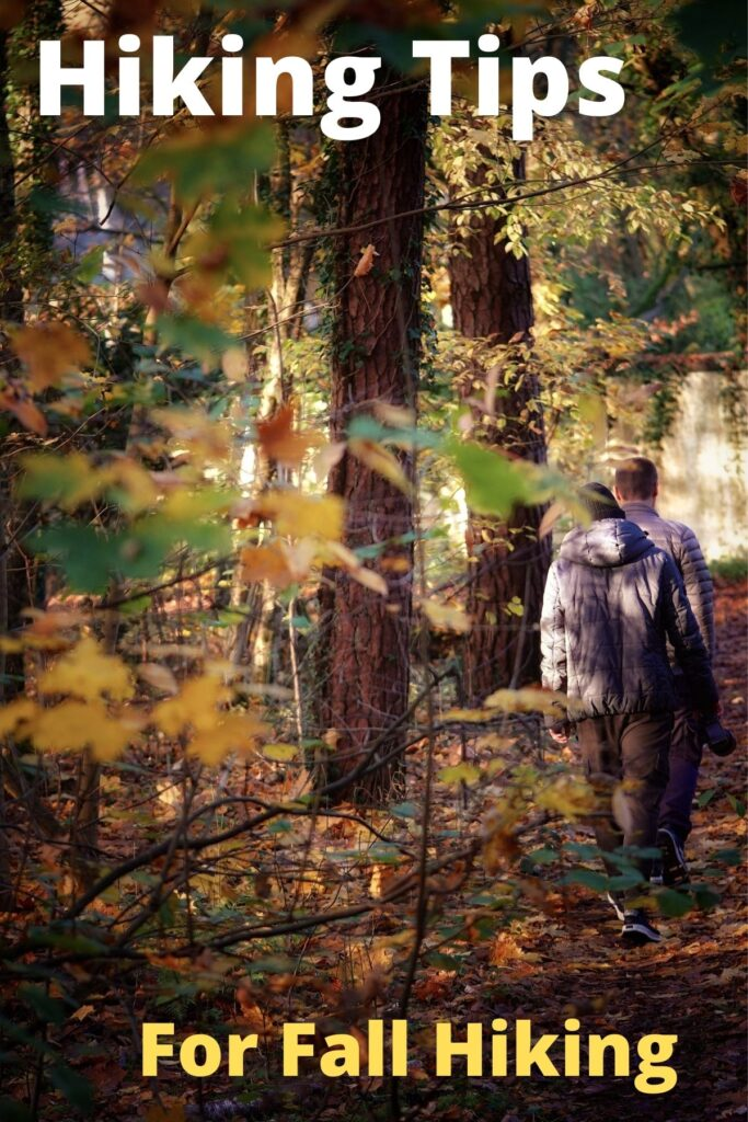 couple hiking in the woods in fall foliage with text overlay 'Hiking Tips for Fall'