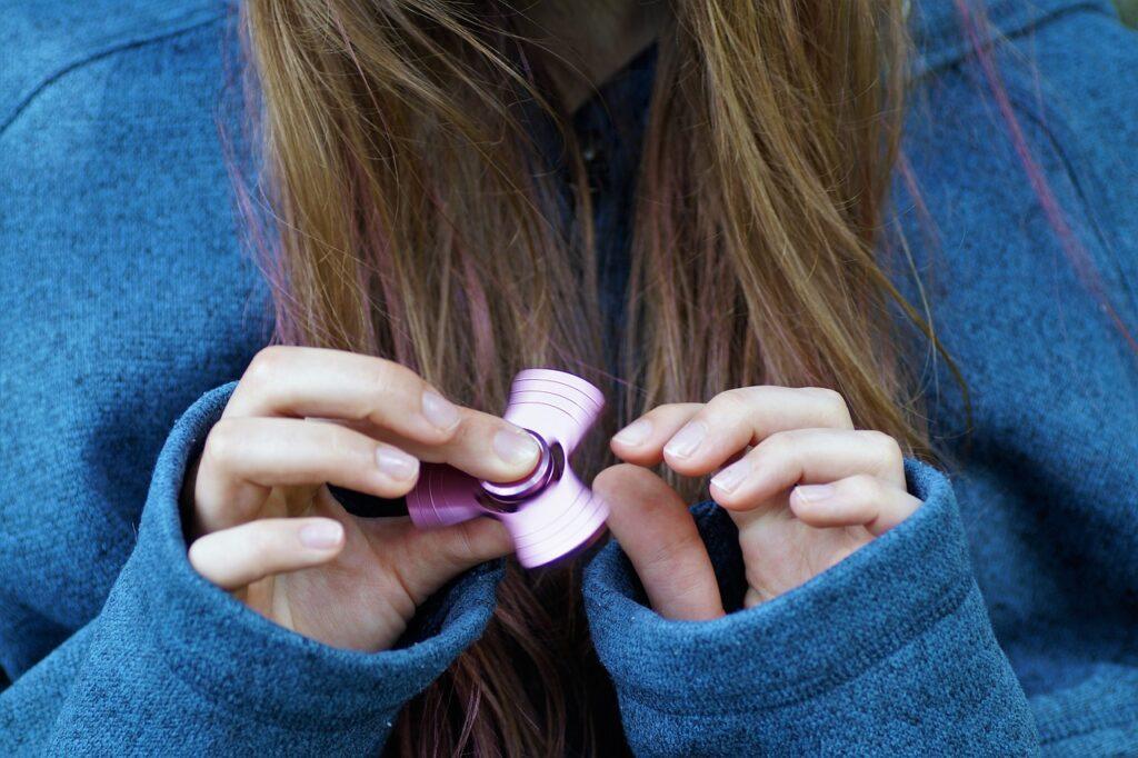 college student holding fidget spinner