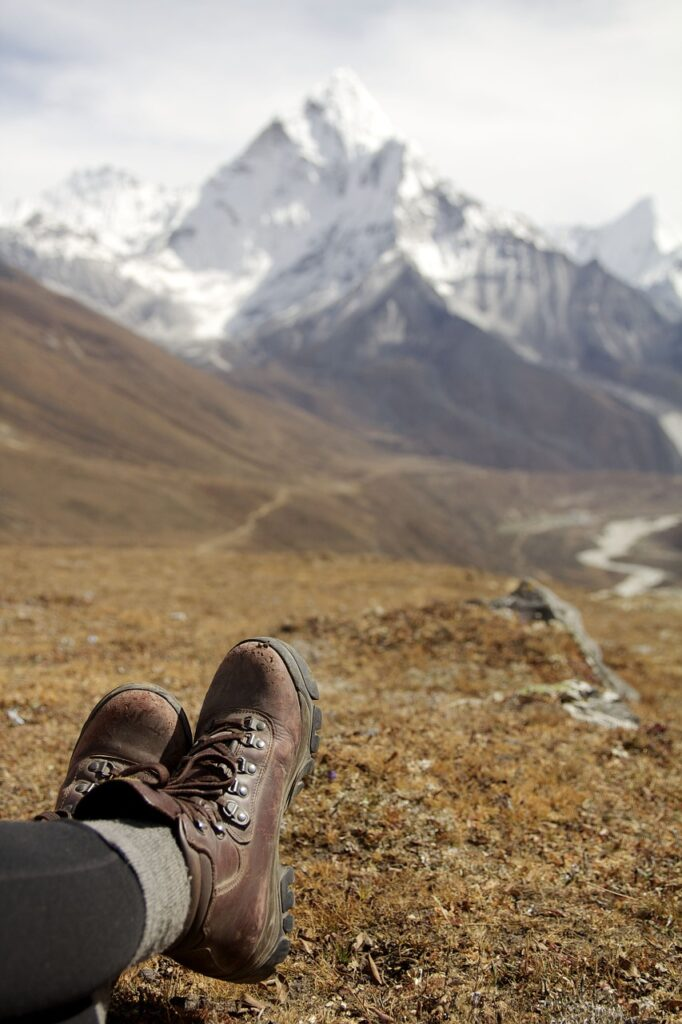 close up of hiking boots on open grassy area with mountains in background