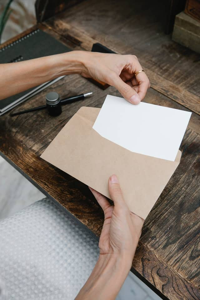 person putting letter to college student in envelope