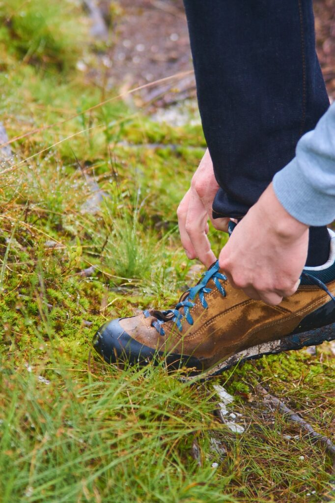 person tying hiking boot in grass