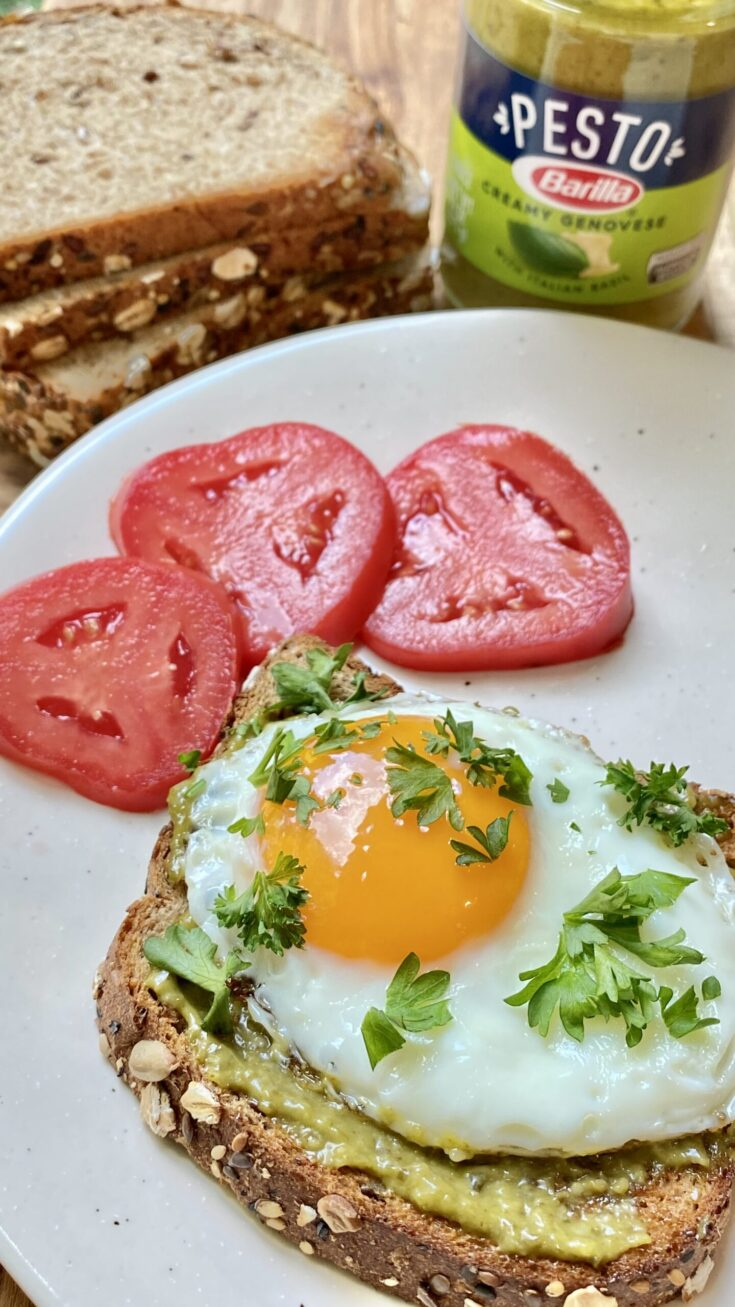 egg pesto toast on plate with fresh tomato slices and jar of barilla pesto sauce in background